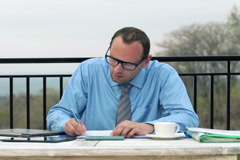 Businessman writing on documents, talking on cellphone on terrace NT Stock Footage