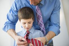 Father adjusting son's(8-9) tie Stock Photos