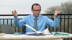 Businessman overwhelmed by to much paperwork by the table on terrace HD Stock Footage