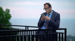 Young businessman using, texting on smartphone on terrace HD - stock footage