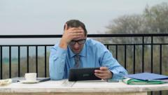 Unhappy businessman reading bad news from stock market on his tablet HD Stock Footage