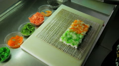 Rolling up the sushi roll with red and green tobiko, upside view Stock Footage