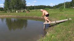 Men and girl jump in turn in pond from footbridge on countryside Stock Footage