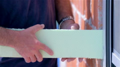 Pushing styrofoam around window for isolation house Stock Footage