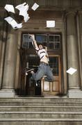 Student Throwing Papers in Air By School Stock Photos