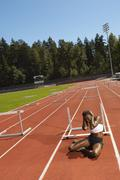 Woman Sitting on Running Track after Stumbling Stock Photos