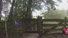 Man walks through gate shutting it behind him. Stock Footage