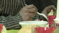 Homeless man eats a free lunch at the community center. Stock Footage