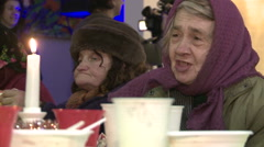 Homeless old woman eats a free free Christmas dinner in a community center. - stock footage