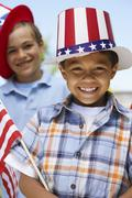 Stock Photo of Portrait of Boy Wearing Stars and Stripes Hat Holding Flag