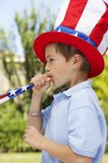 Stock Photo of Portrait of Boy Wearing Large Stars and Stripes Hat, Blowing Noisemaker Horn