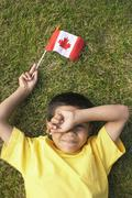 Portrait of Boy Lying on Grass, Holding Canadian Flag - stock photo