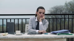 Bored, lazy businesswoman sitting by the table on terrace HD Stock Footage