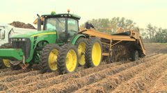 Tractor pulling potato harvester Stock Footage