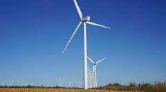 Worms eye view of Wind turbines and track, blue sky Stock Footage