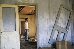 Man in Decrepit House - stock photo