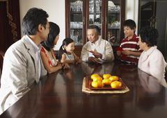 Family Sitting around Dining Table Stock Photos