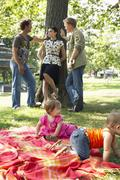 Men Talking to Woman while Babies Play in Park Stock Photos