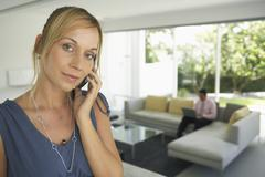 Woman Using Cellular Phone, Man in Background - stock photo