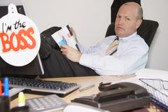 Portrait of Boss Reading Magazine at Desk Stock Photos