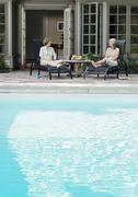 Women Lounging By Pool - stock photo