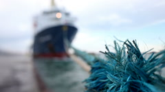 Handheld close up of ship's blue rope at anchor in a harbor. Stock Footage