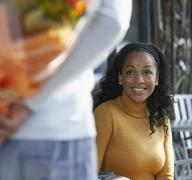 Woman Looking at Man Holding Flowers Behind Back - stock photo