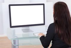 rear view of businesswoman using computer at desk in office - stock photo