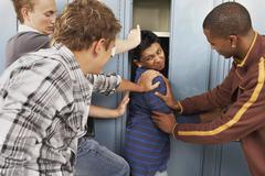 Group of Teens Stuffing Boy in Locker Stock Photos