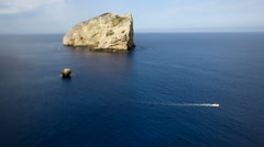 Boats sailing with a white wake near a rock on a blue sea. Stock Footage
