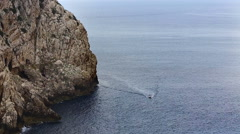 Wide angle shot of boat sailing near a rock. Stock Footage