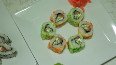 Panoraming shot of delicious sushi rolls on white plate with wasabi and ginge Stock Footage