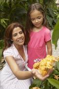 Portrait of Mother and Daughter Looking at Flowers Stock Photos