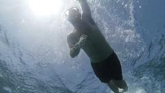 Stock Video Footage of Man swimming on ocean surface view from below 2