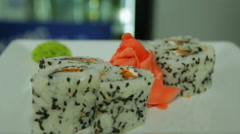 Dolly shot of delicious sushi rolls on white plate with wasabi and ginger - stock footage