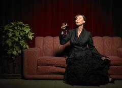 Woman Raising Glass of Red Wine Stock Photos