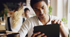 Mixed race man using digital display touchscreen tablet ipad device in cafe Stock Footage