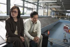 Couple Waiting for Luggage, Vancouver, British Columbia, Canada Stock Photos
