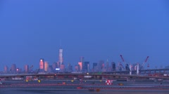 Planes taxi at Newark airport at dusk with the Manhattan skyline background. Stock Footage