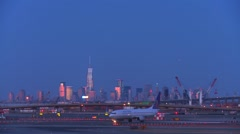 Planes taxi at Newark airport at dusk with the Manhattan skyline background. - stock footage