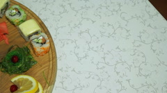 Panoraming of delicious sushi rolls on wooden plate decorated with wasabi, gi - stock footage