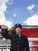 Fire Chief Saluting by Fire Truck - stock photo