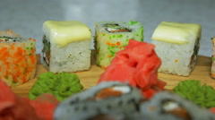 Dolly shot of delicious sushi rolls on wooden plate with wasabi and ginger - stock footage