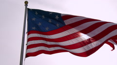 An American flag waves in slow motion with the sun behind. Stock Footage