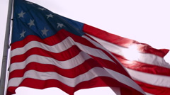 An American flag waves in slow motion with the sun behind. - stock footage