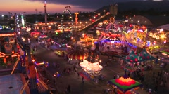 A high angle view over a brightly lit amusement park with many rides and - stock footage