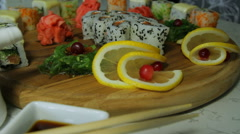 Dolly shot of delicious sushi rolls on wooden plate with wasabi and ginger Stock Footage