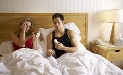 Couple in Bed, Woman Taking Pills - stock photo