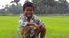 Cambodian Boy Sitting on Rice Field, Smiling Stock Footage