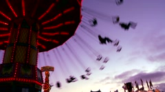 A merry go round spins with riders against the sky. Stock Footage